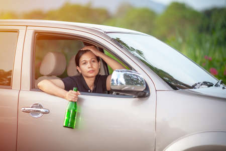 dangerous driving - young woman drinking beer and driving car,  drinking alcohol in vehicle and road accidents concept
