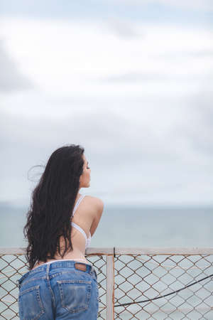 sexy girl standing posing and watching the ocean
