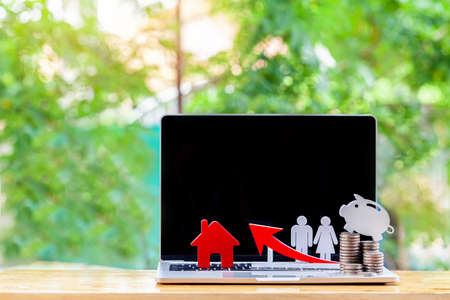 laptop with blank screen and coin near house model on wooden desk,