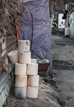 shantytown: Used coal briquette on the street