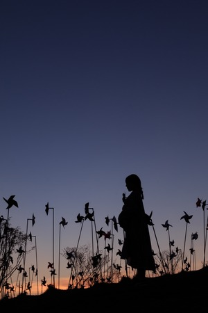silhouette of asian pregnant woman in the middle of pinwheel field