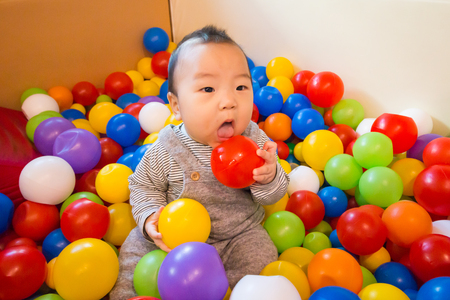 baby asian playing in colorful ball pool (ball pit)