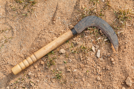 Rusty Korean sickle on the ground. Agricultural tool