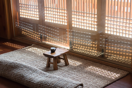 Korean traditional wooden tea table with sunlight through tradional door gratings
