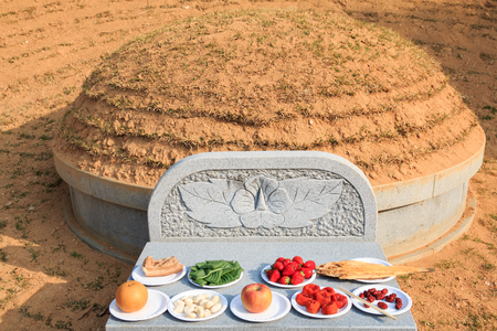 Korean gravesite with foods and fruits on the altar