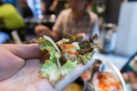 Korean BBQ, meat wrapped in lettuce on a hand Zdjęcie Seryjne