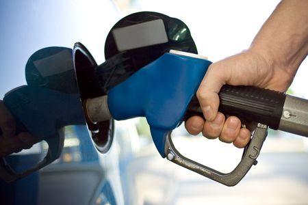 refilling: close-up of a mens hand refilling the car with a gas pump
