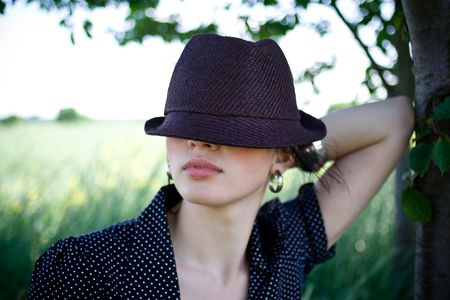 hides: girl hides behind her hat Stock Photo