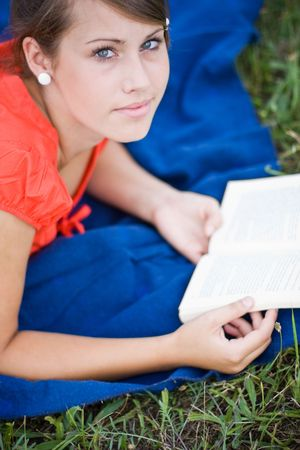young girl relaxing and reading a book photo