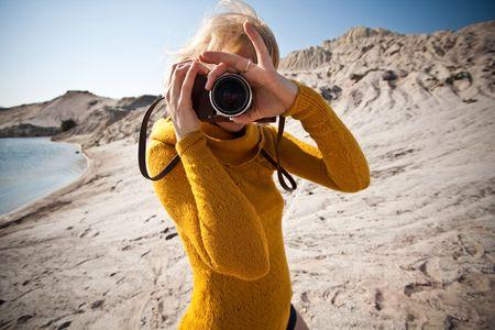 aficionado: mujer con una vieja c�mara de tomar fotos en el desierto