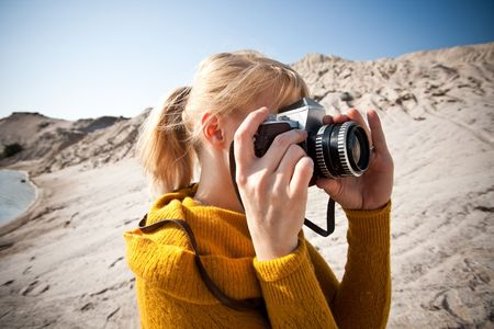 woman with a old camera taking photos in the desert photo