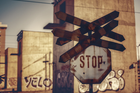 old sign: Old and rusty rail crossing stop sign. Dark apocalyptic scene. Stock Photo