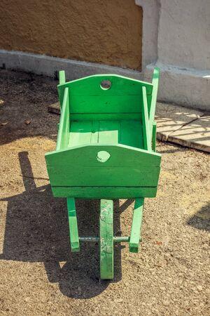 carretilla de mano: Primer plano de la vieja carretilla de mano verde decorativa hecha a mano de madera. Foto de archivo