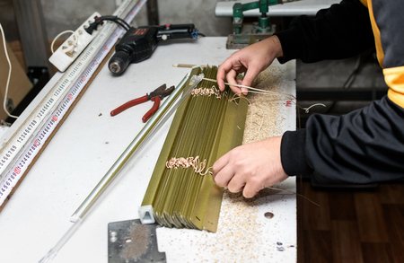 sipario chiuso: Man working on Venetian blind assembly at home workshop. Archivio Fotografico