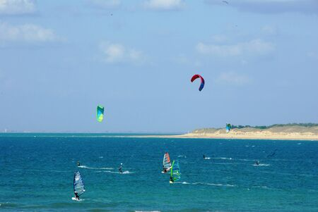 windsurfers: Windsurfer and kitesurfer in the sea off the island of R Stock Photo