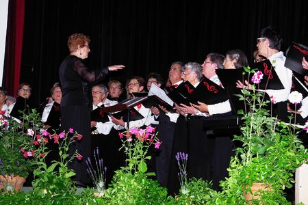Choir on a stage with a black background