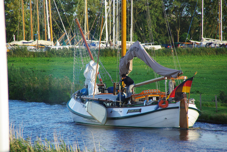 sailboat navigating the engine on a canal in Holland 報道画像