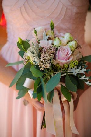 Bridesmaids bouquet of pink and cream  flowers against a pink dress. Foto de archivo