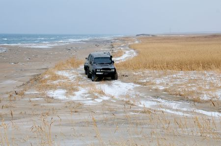 SUVs on winter roads against the backdrop of stormy sea. Off-road on Khasansky swamps in the border zone. Stock Photo - 7996633