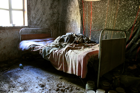 Bedroom with iron bed, old blankets and dirty interior in an abandoned house. After war and natural disaster concept.