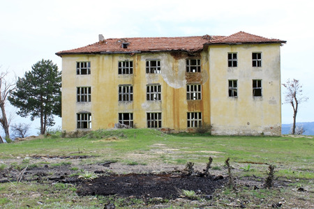 broken hill: Haunted abandoned building of old public school with no windows on green hill. Horror and after war concept. Stock Photo
