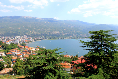 Aerial view of Ohrid Lake, city of Ohrid and mountains in the background. Pine-trees in the foreground. Ohrid is a Macedonian resort and famous tourist destination under the auspices of UNESCO