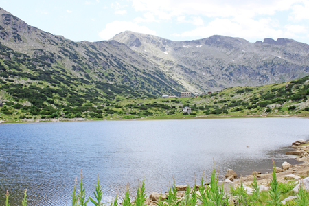 View of Ribno Lake high in the Rila Mountains, Bulgaria. Mountain huts faraway in the background.