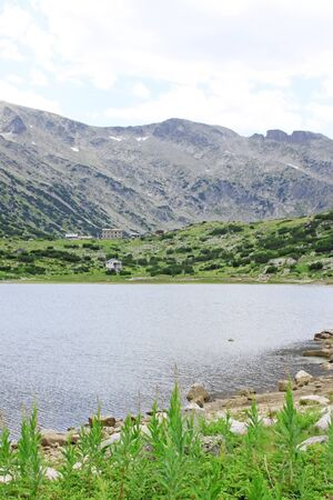 faraway: View of Ribno Lake high in the Rila Mountains, Bulgaria. Mountain huts faraway in the background.