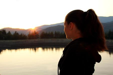 mujer mirando el horizonte: Mujer joven por el lago viendo la puesta de sol en las monta�as. Foto de archivo