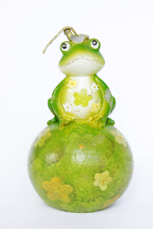 Green frog candle decorated with flowers seating on a green ball isolated on white background.