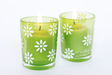 easter candle is burning: Two burning candles in green glass jars isolated on white background. Stock Photo