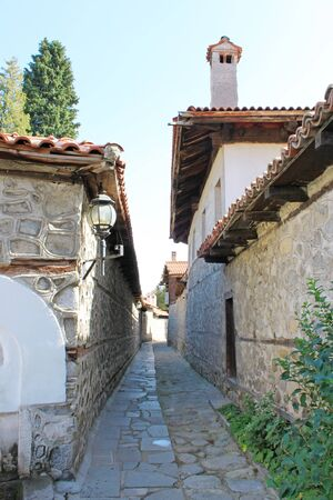 stoned: Stoned street in the old town in the center of Bansko, Bulgaria with traditional architecture. Bansko is a town in southwestern Bulgaria, located at the foot of the Pirin Mountains. It is a popular ski resort for both European and Bulgarian tourists.