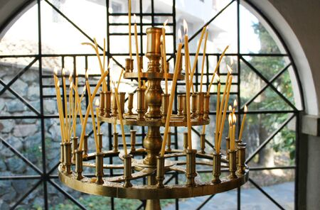 Orthodox church wax candles in chandelier burning in front of the window. Photo taken in Dragalevtsi Monastery, Bulgaria. Editorial
