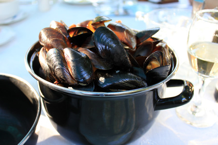A black pot with steamed mussels in shells with a glass of white wine aside.