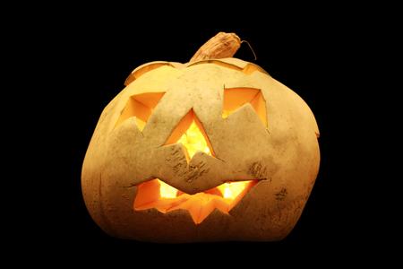 pumkin: Carved Halloween pumkin illuminated from inside isolated on black background