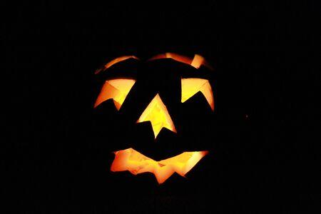 pumkin: Illuminated carved pumkin in the dark isolated on black background. Halloween concept