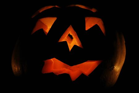 Illuminated carved Halloween pumkin close up isolated on black background