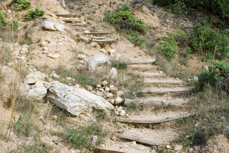 ascending: Hiking trail with wooden stairs ascending the hill. Photo taken in Melnik area, Bulgaria Stock Photo