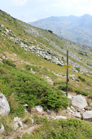 trail sign: Hiking trail sign on a wooden pole pointing to Vihren hut in the Pirin mountains, Bulgaria
