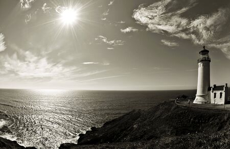 Lighthouse in the Pacific Northwest captured with a sun and ocean scene.  Stock Photo
