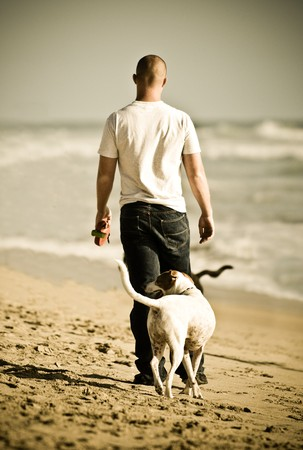 A man walking along the beach with a beagle Stock Photo