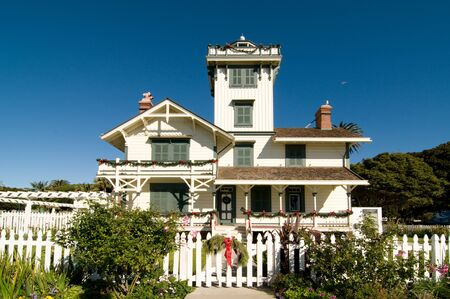 lampost: Historic house with a lampost and shuttered windows, trees, and a bird