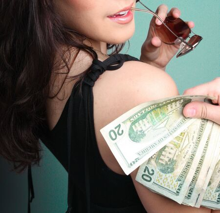woman holding money: Photograph of a young woman holding money bills over her right shoulder.