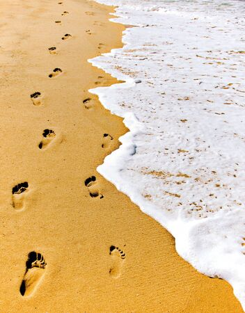 Footsteps in the sand along the surf. Stock Photo