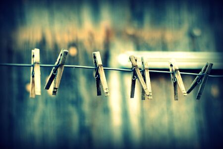 Clothes pins lined up on a wire. Imagens