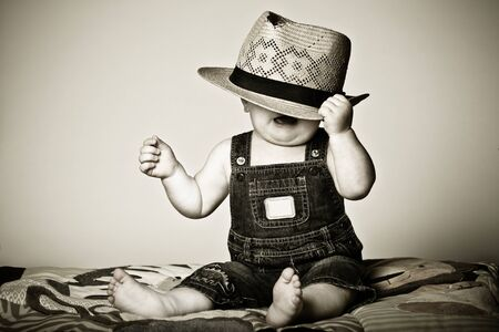 Baby boy under a hat frustrated with the situation. Stock Photo
