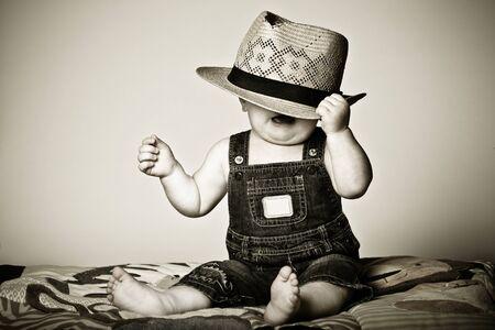 Babyjongen onder een hoed gefrustreerd met de situatie. Stockfoto - 8912041