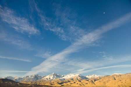 The Eastern Sierra mountain range showing big sky, clouds and the moon in daylight.
