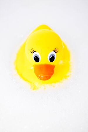 A childs play toy, a rubber ducky in a bubble bath.