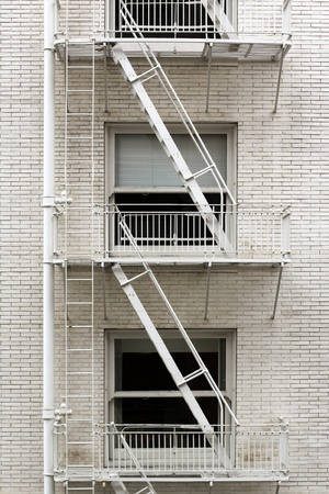 brownstone: Fire escape ladder zigzagging across the face and windows of a brownstone thats been painted white. Stock Photo